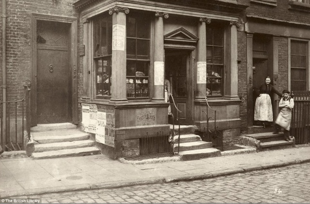 Street scenes like these fascinate me. They show the wear and tear of daily life--the broken window above the door. (Photo: British Library)